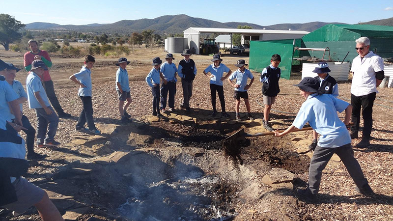 Bingara Central School Stage 3 students take turns to 'damper down' the flames in the biochar fire pit under the guidance of Dr Ruy Anaya de la Rosa and Adam Blakester.