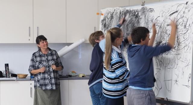 Artist Georgie Pollard watches on while students create a collaborative artwork using charcoal made at TLC.