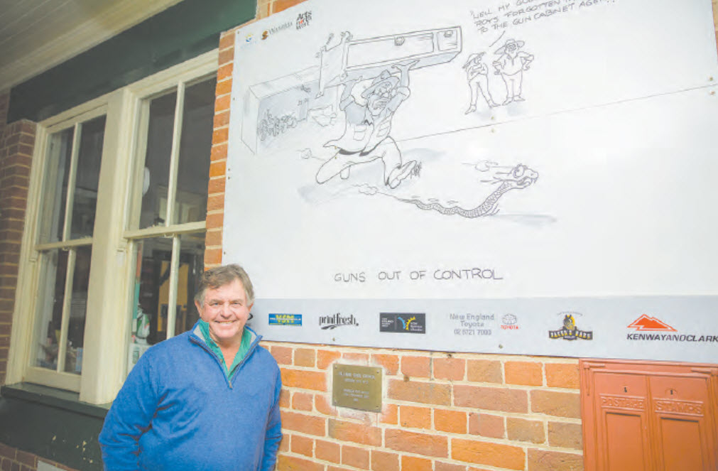 Warialda cartoonist, David Moor with one of his street art installations.
